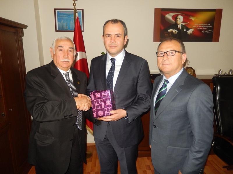 Kocaeli Kandıralılar Derneği Başkanı Erdoğan Görgün ve Günay Gülcü, Derince İlçe Emniyet Müdürü Yusuf Aydın'a Derneğin hediyesini takdim ederken
