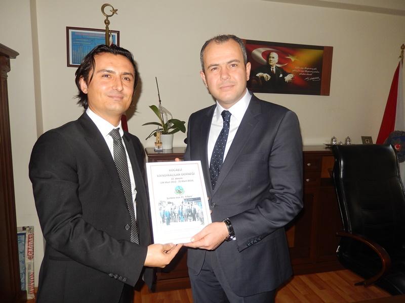 Kuyumcu Onur Altaş, Derince İlçe Emniyet Müdürü Yusuf Aydın'a Derneğin kitabını takdim ederken